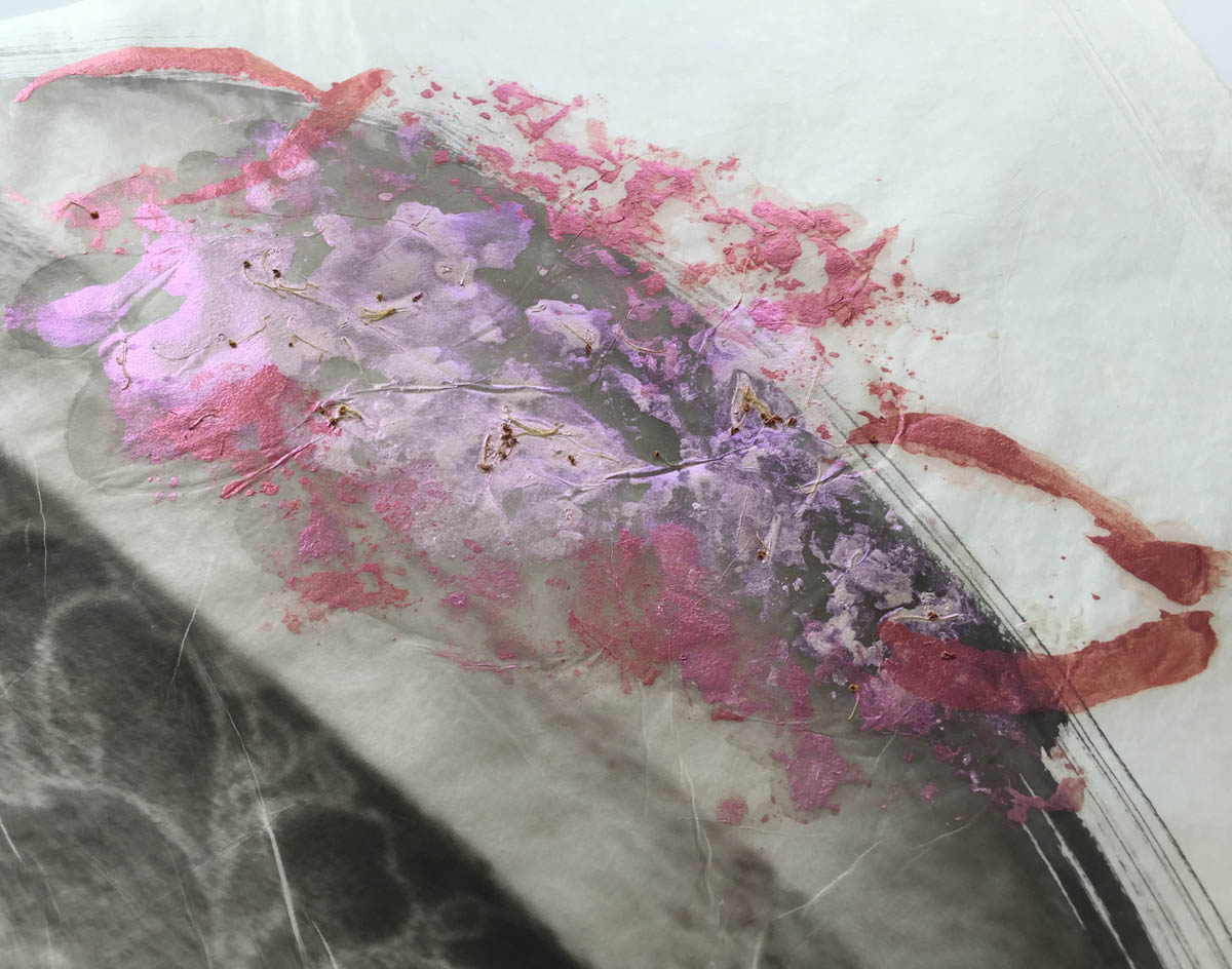 Detail of roses painted on the palladium print of a moth wing with flower tattoos on a woman's arm