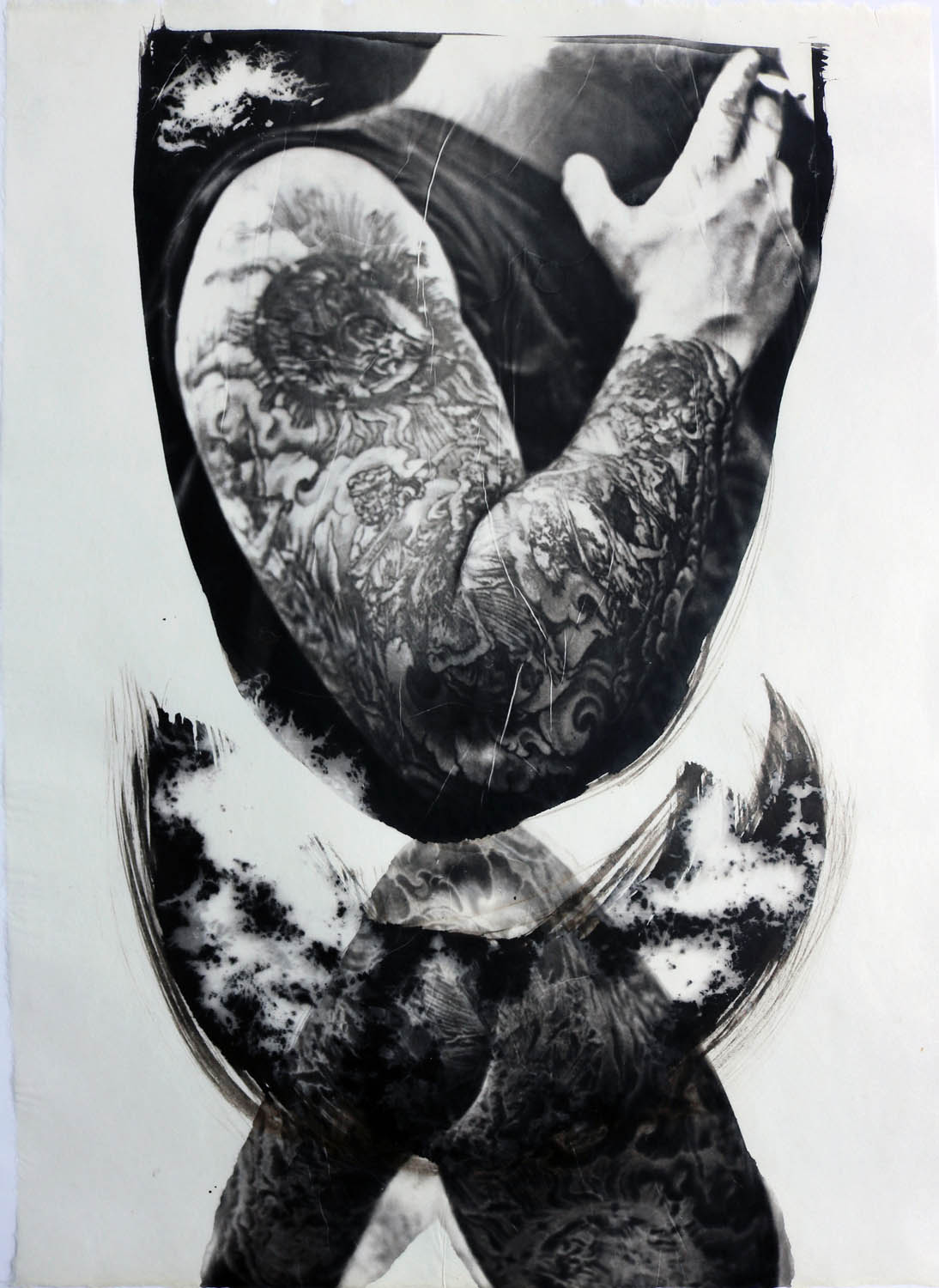 A man who has tattoos derived from Durer's woodcuts of the Apocalypse. His arm is reflected below interrupted by shapes that symbolize the Covid-19 virus that was pandemic worldwide.